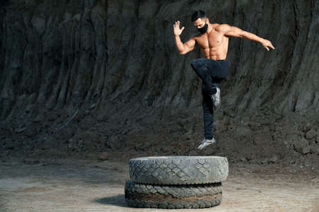 Young shirtless man with athletic body jumping on large black wheel outdoors. Active guy wearing medical mask and sport pants. Concept of fitness and training. Standard-Bild