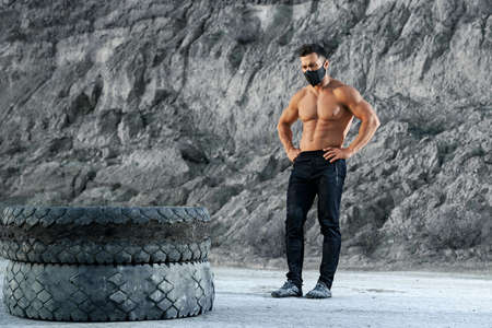 Full length portrait of handsome sportsman wearing black face mask and pants enjoying outdoors training with heavy tyres. Concept of regular workout and healthy lifestyle. Standard-Bild
