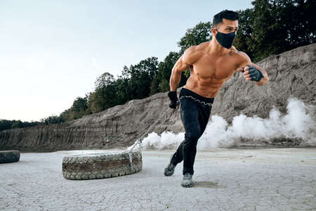 Young sportsman with naked chest in black medical mask using heavy tyre on chain for workout at sand quarry. Concept of sport activity outdoors.
