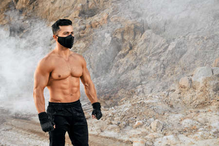 Athletic shirtless man wearing protective mask and sport pants showing his muscular body on camera while standing at sand quarry. Concept of healthy strong male body. 免版税图像