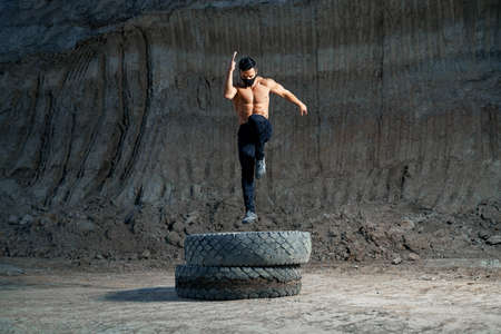 Handsome strong man wearing black medical mask, jumping on large black wheel during evening workout on fresh air. Outdoors training and active lifestyle.