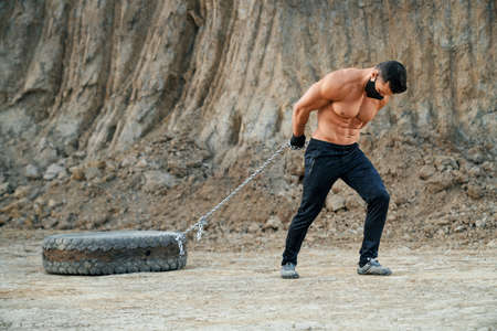 Full length portrait of strong man with naked chest pulling heavy tyre on metal chain among sand quarry. Concept of bodybuilding and sport outdoors.