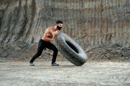 Handsome active guy with muscular naked torso pulling heavy large tyre during outdoor workout. Fit and healthy man in black protective mask having exercises at sand pit. 免版税图像