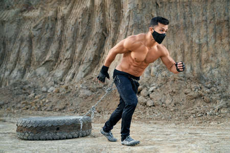 Muscular young man with bare torso exercising outdoors with heavy tire. Strong man in black pants and face mask doing sport activity on sand quarry.