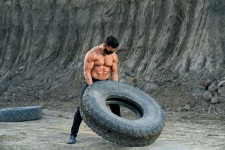Professional bodybuilder in protective mask doing exercises with large black wheel at sand pit. Young man with naked chest leading healthy and active lifestyle. 免版税图像