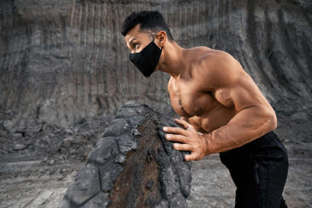 Fit young guy with bare torso workout with large black tyre at sand quarry. Handsome man wearing medical mask while exercising outdoors.