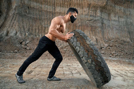 Healthy and young man with athletic body wearing black face mask pulling large wheel outdoors. Concept of sport activity and regular training. 免版税图像
