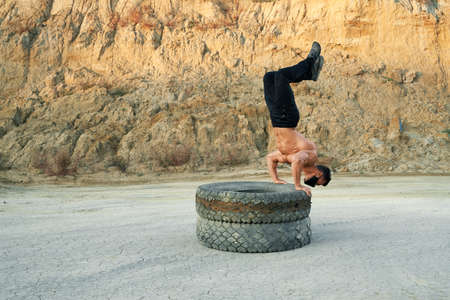Active shirtless guy balancing on tyres and holding legs up while training at sand pit. Muscular man wearing black protective mask during pandemic time.