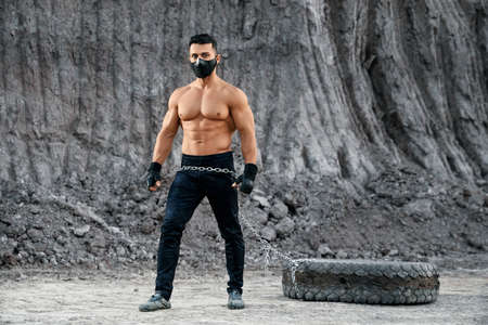 Professional bodybuilder with athletic body shape wearing black mask and sport pants, standing near big tyre at sandpit. Healthy and active man training with heavy equipment on fresh air.