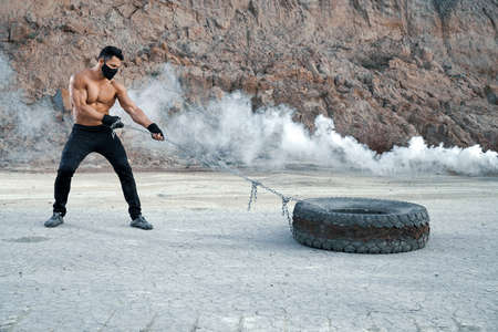Handsome man with athletic body training arms using heavy tyre and chain at sandpit. Active bodybuilder in black protective mask workout alone on fresh air.