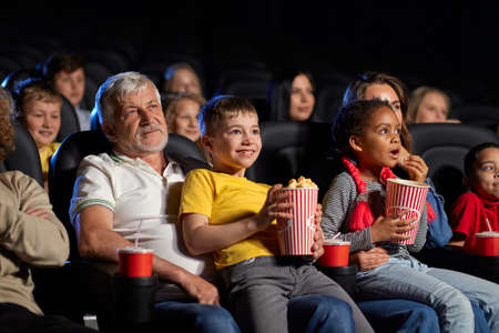 Little african girl with caucasian woman and caucasian boy with senior grandfather. Side view of multiracial kids holding popcorn and sitting on knees of parents. Family, entertainment concept.