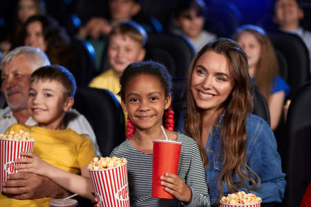 Mother enjoying time with half african little daughter, kid sitting on knees, holding drink and popcorn, looking at camera. Happy multiracial family watching cartoon, grandfather and grandson nearby.