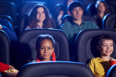 Front view of multiracial kids enjoying time together, young audience on background. Selective focus of happy little african girl sitting in cinema, watching funny cartoon. Entertainment concept.