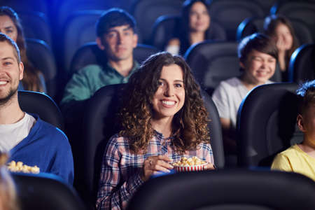 Selective focus of young girl with brown curly hair watching movie in cinema, eating popcorn and laughing. Cheerful attractive caucasian girl enjoying film with friends. Entertainment concept. 免版税图像