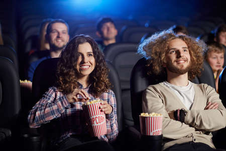 Selective focus of young woman laughing, holding popcorn while watching comedy in cinema. Front view of caucasian man and pretty woman enjoying funny film. Concept of entertainment.