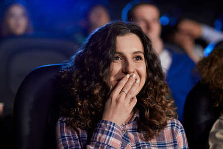 Selective focus of young girl with curly hair watching movie in cinema, laughing and closing mouth with hand. Cheerful attractive caucasian girl wearing striped shirt enjoying comedy with friends. 免版税图像