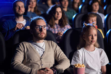 Side view of handsome bearded man in eyeglasses watching serious film with younger blonde sister in cinema, strong faces. Concentrated aucasian female teenager enjoying horror film with family.