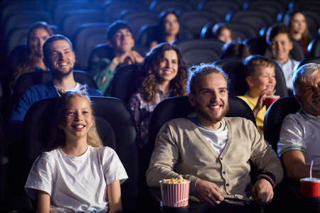 Front view of handsome young boy watching comedy with younger blonde sister in cinema, laughing with teeth. Cheerful caucasian female teenager wearing white t shirt, enjoying film with family.