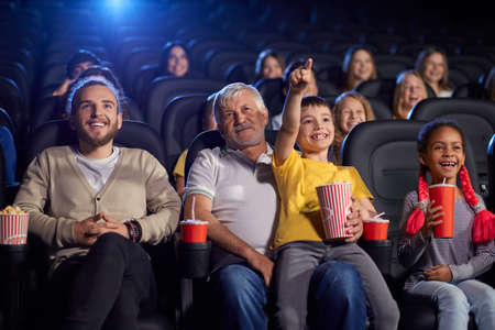 Bearded grandfather with grandson sitting on knees, child holding popcorn and pointing at screen, young multiracial audience laughing. Happy family enjoying time in cinema, watching funny cartoon.
