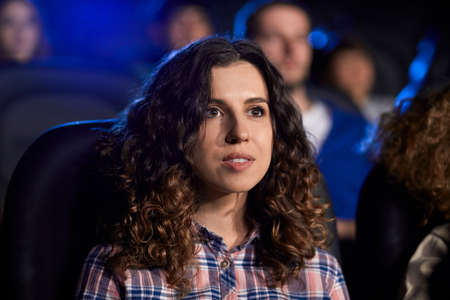 Selective focus of young girl with brown curly hair watching movie in cinema, sitting in comfortable seat. Concentrated attractive caucasian girl enjoying film with friends. Entertainment concept. 免版税图像