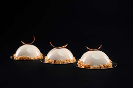 White half sphere cakes decorated with nuts and chocolate feather isolated on black background. Fresh dessert with smooth surface, mousse and mirror glaze. Tasty sweet dish in cafeteria. 免版税图像