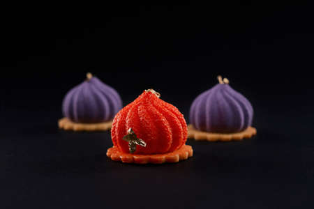 Closeup view of matte purple and orange dessert isolated on black studio background. Three small square cakes in fig shape decorated with gold on top on cookies in restaurant.