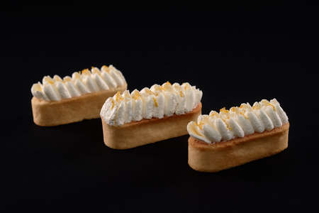 Three fresh homemade biscuit desserts isolated on black background. Shortbread cookies with whipped cream mascarpone topping. Concept of sweets, food industry.