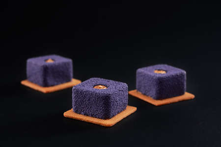 Closeup view of matte purple pie pieces filled with brown creme isolated on black studio background. Three small square matte cakes in row on cookies in restaurant. Sweet bakey, desserts concept.