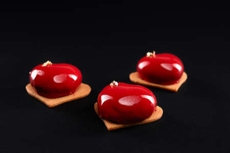 Closeup view of red cakes decorated with gold isolated on black background. Dessert with smooth surface, mousse and mirror glaze on sweet cookies, heart form. Delicious dish in cafeteria.