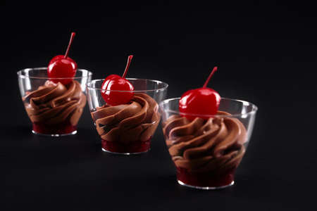 Three small glasses filled with dairy whipped brown chocolate cream and red jam. Closeup view of sweet desserts decorated with fresh cherries on top in row isolated on black background.