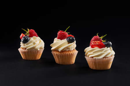 Three fresh tasty vanilla cupcakes in row. Closeup front view of sweet delicious dessert with white creamy topping, strawberry, blueberyy and rasberry slices isolated on black background.