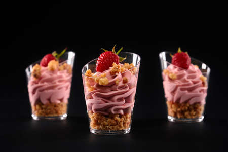 Closeup view of tasty parfait with granola, decorated with raspberries on top and pink whipped cream. Fresh homemade sweet layered dessert in three small glasses in row isolated on black background.