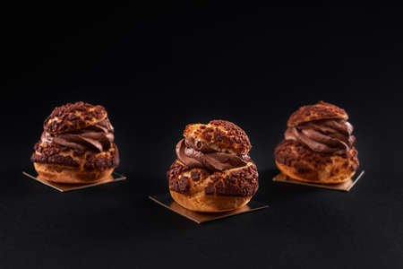 Three delicious fresh crunchy profiteroles with sweet brown chocolate cream inside. Closeup of homemade tasty baked eclairs isolated on black background. Concept of desserts, restaurant food.
