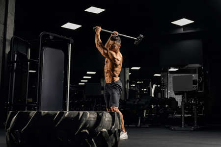 Side view of powerful muscular man hitting giant tire with sledgehammer. Motion of shirtless bearded bodybuilder building muscles in gym in dark atmosphere. Concept of bodybuilding, sport.