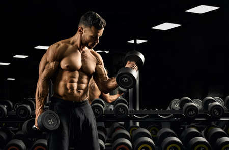 Front view of shirtless bodybuilder training biceps with weights near stand with dumbbells. Close up of muscular sportsman with perfect body posing in gym in dark atmosphere. Concept of bodybuilding.