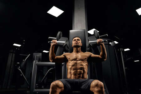 From below view of bearded muscular man sitting on simulator in empty gym. Portrait of shirtless bodybuilder with perfect tensed body training back and looking up. Concept of bodybuilding.