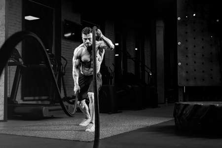 Monochrome portrait of muscular shirtless man doing battle rope training in gym. Crossfit spotrsman with tense face doing power cardio and building muscles. Concept of sport, bodybuilding. Zdjęcie Seryjne