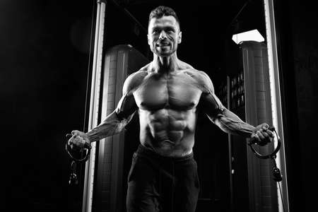 Close up of tensed shirtless bodybuilder training chest in gym in dark atmosphere, monochrome. Crop of muscular man with perfect body doing low cable crossover exercise. Concept of bodybuilding. Zdjęcie Seryjne