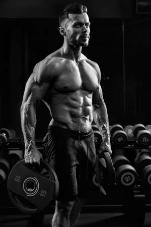 Side view of shirtless tensed incognito male bodybuilder holding weights in arms. Close up of caucasian sportsman with perfect muscular body posing in gym in dark atmosphere. Concept of bodybuilding. Zdjęcie Seryjne