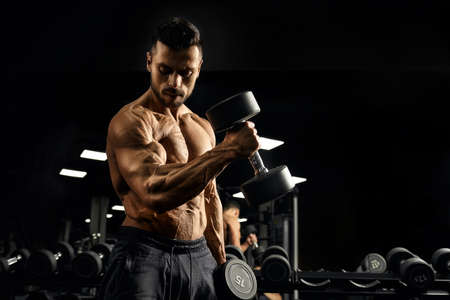 Side view of shirtless bodybuilder training biceps with dumbbell. Close up of muscular sportsman with perfect tensed muscular body posing in gym in dark atmosphere. Concept of bodybuilding.