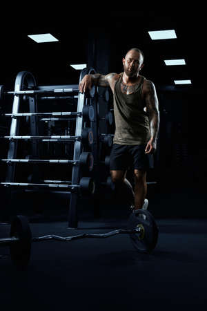 Full length portrait of tensed male bodybuilder in sportswear leaning on stand with barbells. Front view of sportsman with perfect muscular body posing in gym in dark atmosphere and looking at camera.