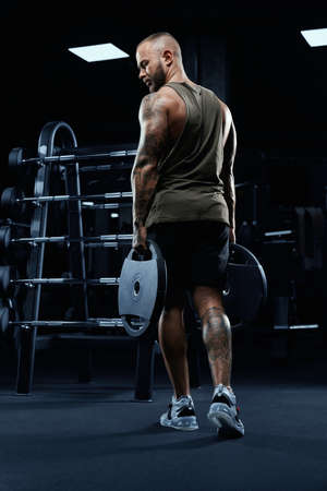Portrait of tattooed tensed male bodybuilder holding weights in arms, looking down. Back view of sportsman with perfect muscular body posing in gym in dark atmosphere. Concept of bodybuilding.