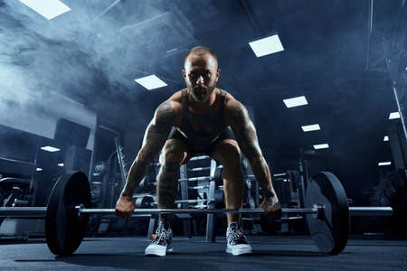 Front view of bearded bodybuilder training legs with barbell. Muscular tattooed sportsman with perfect body doing deadlift, posing in gym in dark atmosphere. Concept of bodybuilding.