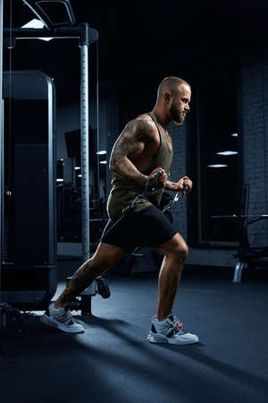 Portrait of muscular bearded bodybuilder doing low cable crossover exercise. Side view of man with perfect body training chest in gym in dark atmosphere. Concept of bodybuilding.