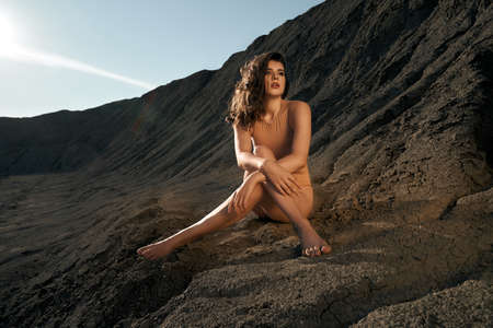 Front view of astonishing caucasian female model posing in dry empty quarry in hot summer sunny day. Young barefoot stylish woman sitting with legs crossed on black sand outdoors and looking aside.
