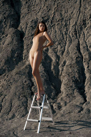 Full length view of young female model with nice figure wearing beige body posing on ladder outdoors. Stunning brunette woman with hand on waist looking at camera. Fashion, beauty concept.