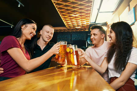 Side view of happy company sitting together in pub and drinking beer at weekend. Cheerful young male and female looking at each other, talking and laughing in bar. Concept of fun and happiness.