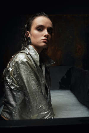 Side view of wet brunette girl sitting in bath with muddy white water. Monochrome portrait of young female with perfect makeup in silver jacket posing and looking at camera. Concept of modeling.