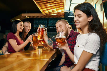 Side view of young smiling brunette enjoying free time with happy friends and drinking beer in bar. Cheerful company drinking alcohol, talking and laughing in pub. Concept of beverage and fun. Stock fotó