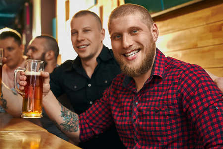 Happy male hipster with tattoo keeping glass of beer, looking at camera, smiling and posing in cafe. Young man drinking alcohol with friends, resting and enjoying evening. Concept of fun.